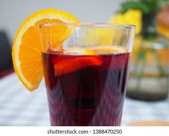 Mulled wine with orange, drink cozy and delicious. Drink and cocktail concept. Glass with mulled wine near juicy orange fruit on light background. Drink or beverage with orange.