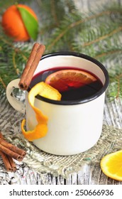Mulled wine with orange and spice in enamel mug.