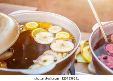 Mulled wine prepared in iron pot at city street fair. Traditional christmas and new year alcohol drink - hot wine. Stall with drinks in town at winter holiday fest