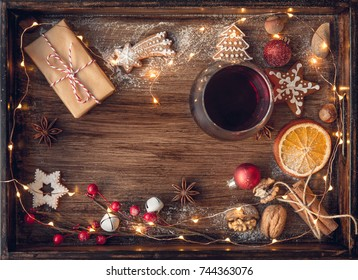Mulled wine or punch in glass, christmas cookies, dry oranges and lights on dark rustic vintage background, top view, border. Christmas concept.