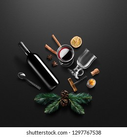 Mulled wine recipe ingredients and kitchen accessories, bottle of red wine, cinnamon, anise stars, orange, brown sugarand spice on black background.