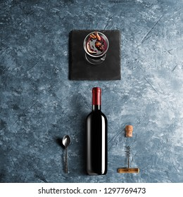Mulled wine recipe ingredients and kitchen accessories, bottle of red wine, cinnamon, anise stars, orange, brown sugarand spice on blue stone background.