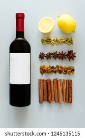 Mulled wine recipe ingredients on gray wooden table. Christmas or winter warming drink. Bottle of wine, lemon, cinnamon sticks, anise, cardamon, raisin. Top view. Flat lay