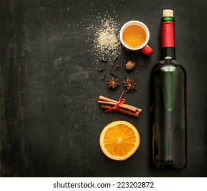 Mulled wine recipe ingredients on black chalkboard with text space - christmas or winter warming drink. Bottle of wine, honey, orange, cinnamon sticks, anise, nutmeg, cloves and sugar from above.