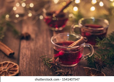 Mulled wine, glühwine or scandinavian glögg. Three cups of warm winter drink for christmas. On a dark brown table. With cozy string lights in the background.