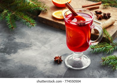 Mulled wine with spices and Christmas tree on dark background.