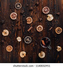 Mulled wine with spices and dried fruits on wooden background