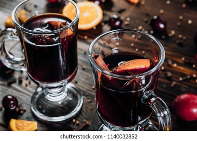Mulled wine with spices and fruits on wooden background
