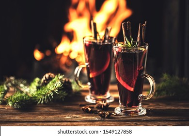 Mulled wine with spices in glasses on a wooden table against the background of a fireplace fire. Winter drink traditional for the Christmas holidays.