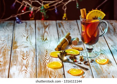 Mulled wine with spices on a wooden table and a garland.