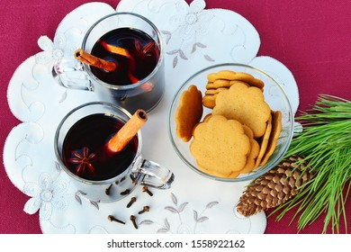Mulled wine in two glass mugs with cinnamon sticks, star anise, cloves and gingerbread cookies on plate.
