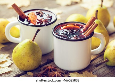 Mulled wine in white rustic mugs with spices and pear fruits. Autumn still life. Vintage stylized.