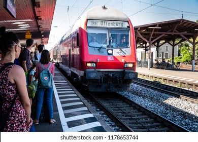 Mullheim, Baden-Wurttemberg, Germany - JULY 30 2018 : DB Regional train from Basel (Switzerland) to Offenburg (Germany) arriving at the Mullheim station while passengers are waiting on the platform