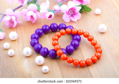 multi color coral bangles and artificial pearls, with pink flower on wooden background