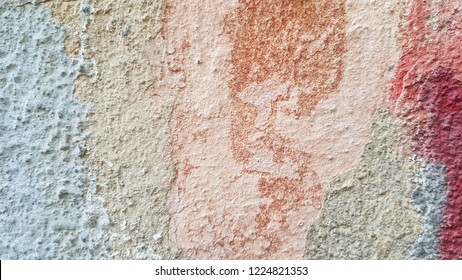 Multi color distressed scratched background in shades of beige and light blue grey with red stain. Rough textured plaster wall surface closeup. Old stucco texture. Grunge background. Shabby backdrop.