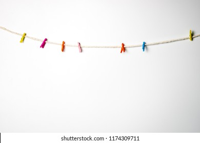 Multi Color wooden clip hanging with white rope with white background.