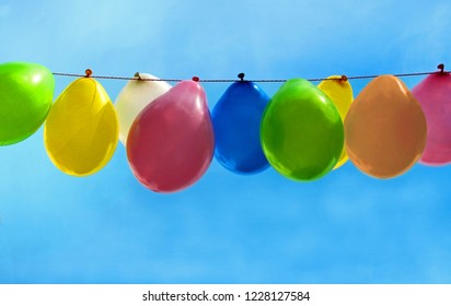 multi colored balloons hanging in front of blue sky, cheerful background for birthday, party or greeting card
