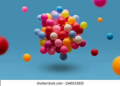 Multi colored balls levitation in mid air on blue background.