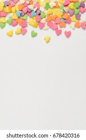 Multi colored candy hearts scattered on light paper