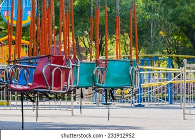Multi colored chain carousel chairs  in amusement park at noon .
