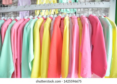 Multi colored clothing hanging on hangers, children's clothing store, colorful shirt