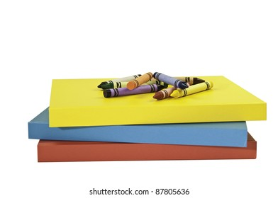 Multi colored crayons on top of a yellow,blue and a red book. This has a clipping path.