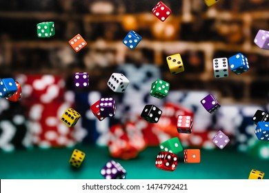 Multi Colored dice Chips cascading in front of a background of stacked poker chips.  Depth of field is medium, so many dice are in focus and many others are not.