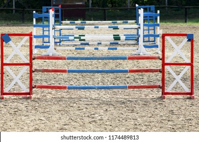 Multi colored image of show jumping poles at the show jumping arena. Wooden barriers for jumping horses as a background
