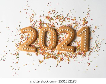 Multi colored pastry sugar topping and gingerbread in the form of numbers 2021 on a white background.  2021 new year ginger cookies