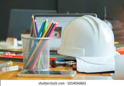 Multi colored pencils in box with safety helmet, smart phone and laptop on the desk.