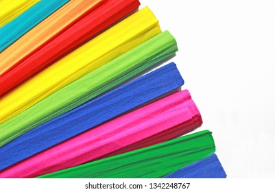 multi colored rolls of crepe paper fanned out on white background