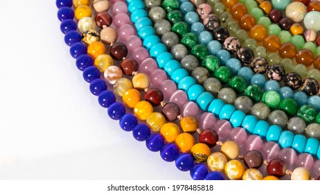 Multi colored shiny beaded necklaces made of natural stones on a white background.  Stone texture, pattern, background. Isolated jewelry, bright colors, energy stones, handmade beads.