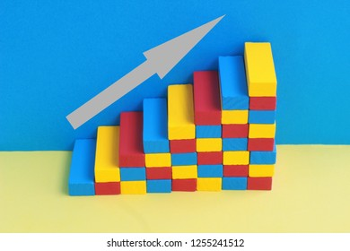 multi colored stairway, formed by wooden toy blocks, in front of a blue wall, gray arrow pointing up the stars