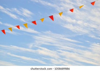 Multi Colored Triangular Flags Hanging in the Sky