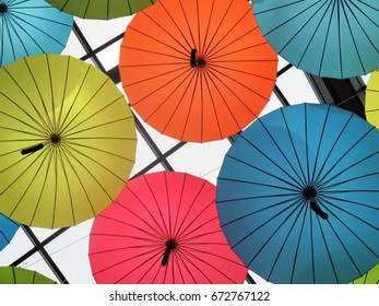 Multi colored umbrellas hanging from a ceiling in a mall