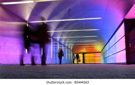 multi colored underground tunnel with people in motion