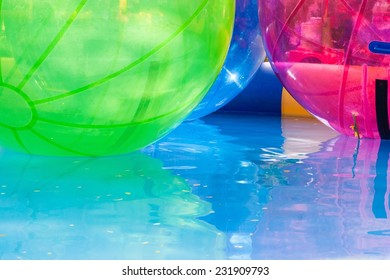 Multi colored water zorbing balloons in the pool with no kids inside.