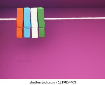 Multi colorful wooden clothespin on purple gradient background
