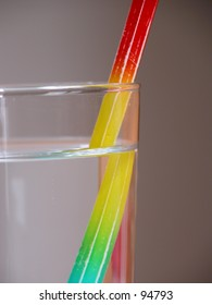 Multi coloured pencil in a glass of water, depicting refraction, illusion.