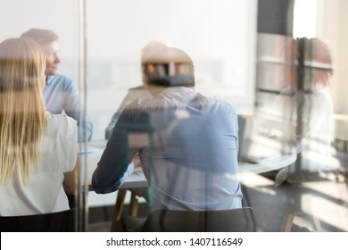 Multi ethnic business people negotiating sitting at conference table, diverse staff employees talk at team private meeting in modern office boardroom, colleagues group collaborate, view through glass