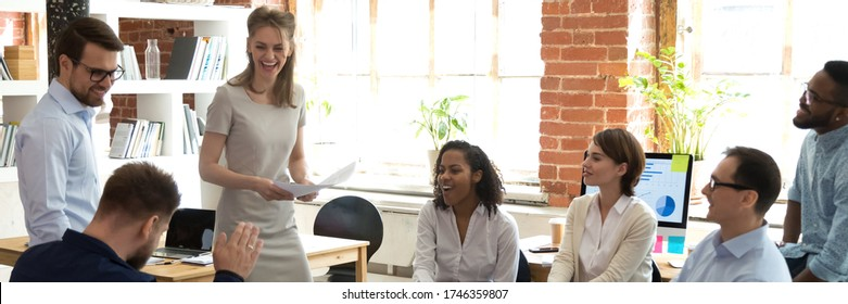 Multi ethnic business team having fun at group meeting. Participation at team building, employees laughing at briefing or corporate training concept. Horizontal photo banner for website header design