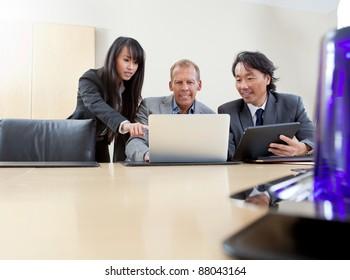 Multi ethnic business team working on laptop