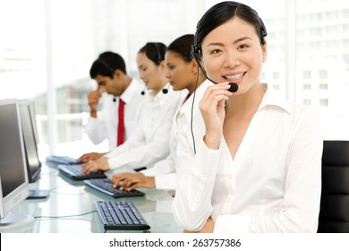 Multi ethnic Call Center. Selective focus on Asian woman on foreground.