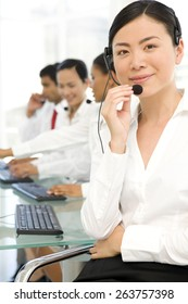 Multi ethnic Call Center team. Selective focus on Asian woman on foreground