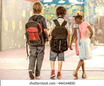 Multi ethnic classmates walking in schoolyard, seen from behind.