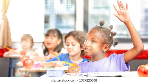 Multi ethnic classroom in primary school. African girl raising hand, sun rays coming from outside.