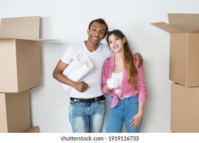 Mehrethnische Ehepaare in einer neuen Wohnung während des Umzugs mit einem Plan und Anordnung der Wohnung Blick auf die Kamera. Neues Leben.