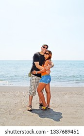 Multi ethnic couple posing with a smile and a hug on the beach during their vacation