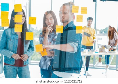 Multi Ethnic Creative team brainstorming in smart casual wear having a meeting while standing behind the glass wall at the office