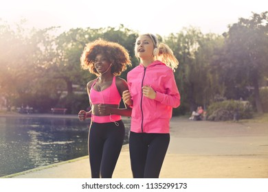 Multi ethnic female friends running in a park